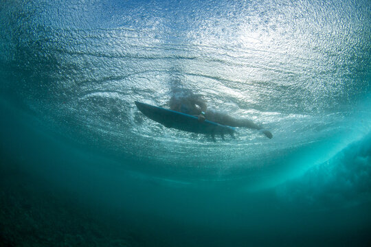 A feamle surfer is duck diving under a wave in Bali. Bubbles are surrounding her.