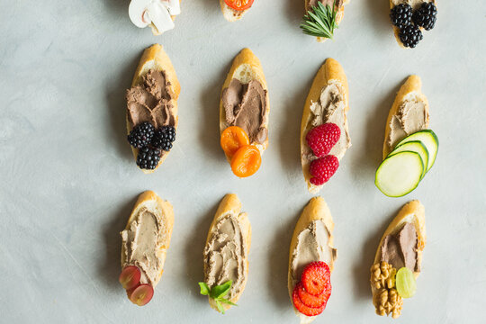 Colored bruschetta with pate, berries, dried fruits.