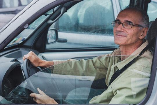 elderly man looking at camera from car window