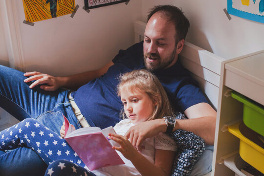 family time on weekend, father and daughter reading book together at home