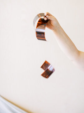 Hand holding 120 film strips against peach backdrop