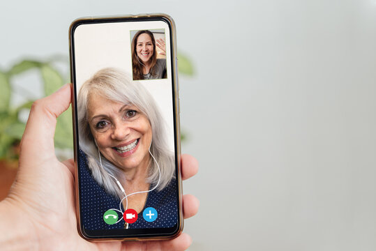 Happy senior and daughter talking on video call with mobile phone during coronavirus outbreak - Online app and social distancing concept - Focus on faces
