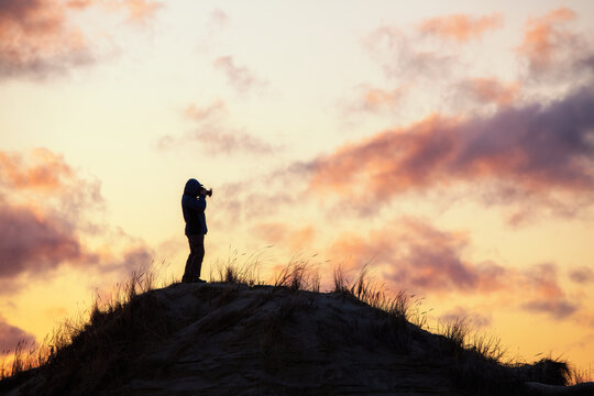 Photographer silhouette on sunset sky background