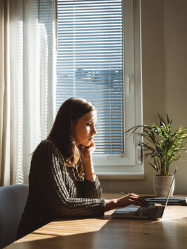 Woman working on her laptop at home next to the window