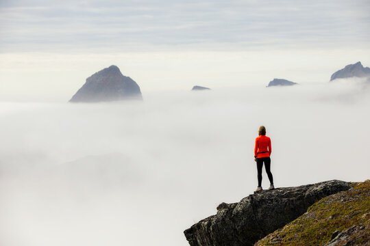 A girl stands on the edge of a cliff with panoramic views of the fjords and mountains