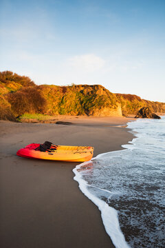 Kayaks at the beach during sunrise.