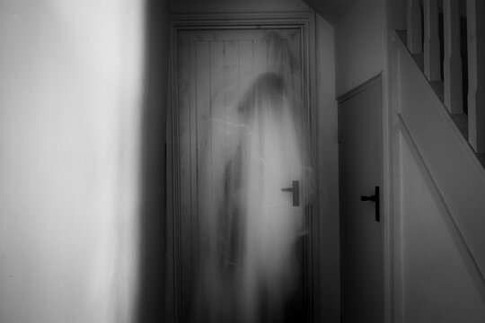 A ghostly, blurred, hooded figure. standing in a corridor.