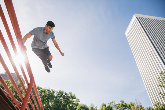 Young man jumping over railing performing parkour against clear sky in city
