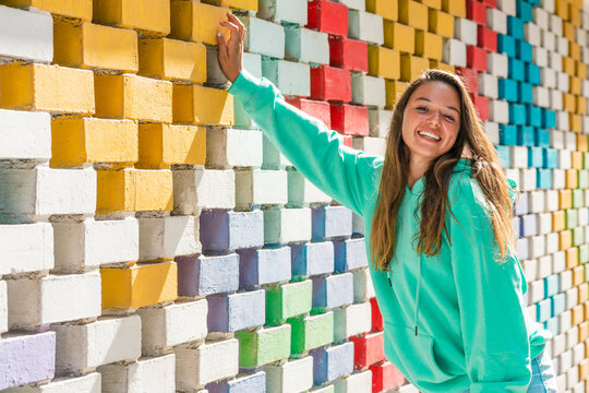 Smiling young woman standing by colorful brick wall on sunny day
