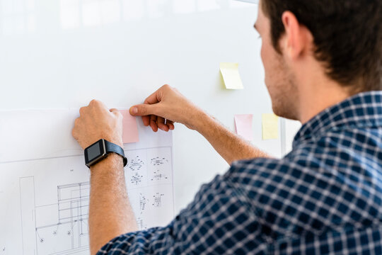 Man putting adhesive note on whiteboard while standing at office