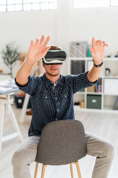 Young man with arms raised using visual reality simulator while sitting on chair at office
