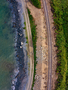 Aerial view of empty railroad tracks stretching along coast