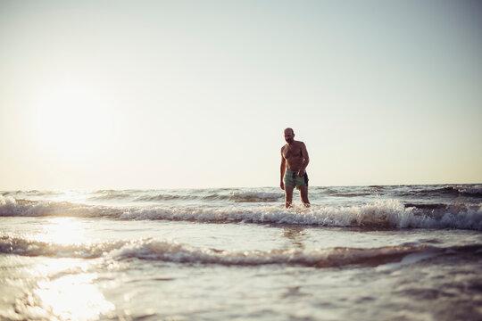 Senior man walking in water at beach