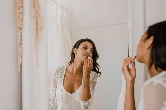 Young bride applying lipstick while looking in mirror at home