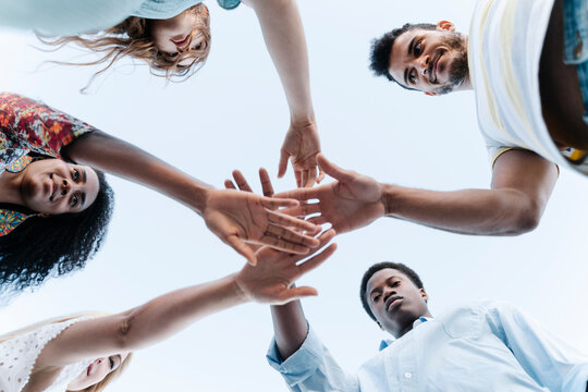 Low angle view of friends bring their hands together in show of unity before playing game