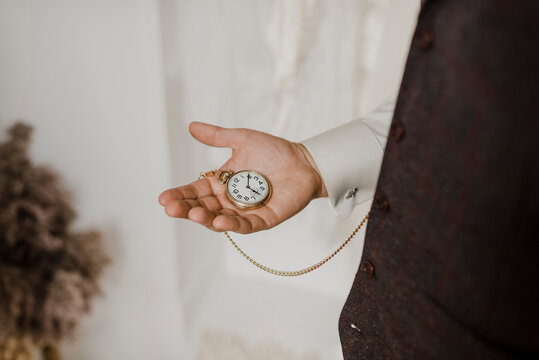 Midsection of bridegroom holding chain watch in hand
