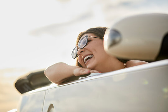 Cheerful woman laughing while sitting in convertible car for road trip
