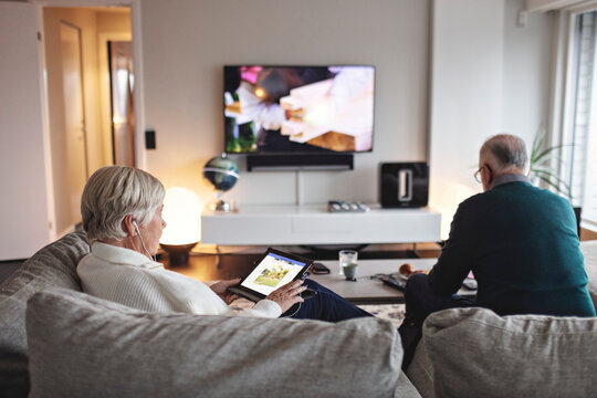 Senior woman using digital tablet while partner sitting on sofa in living room
