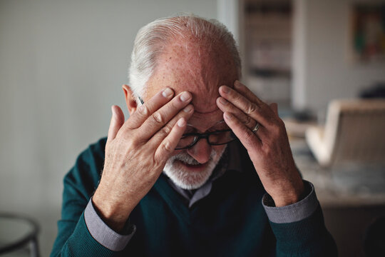 Worried senior man with head in hands at home