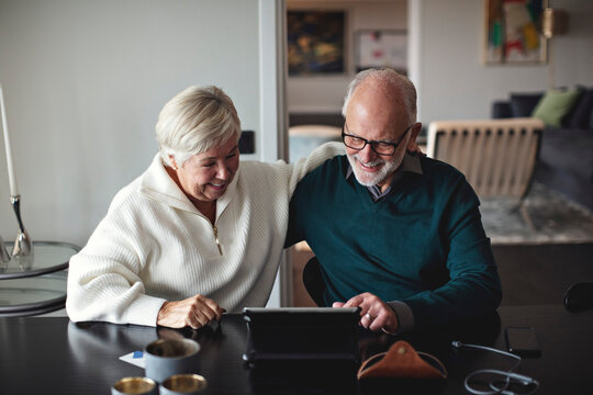Smiling senior couple using digital tablet while sitting by dining table in living room