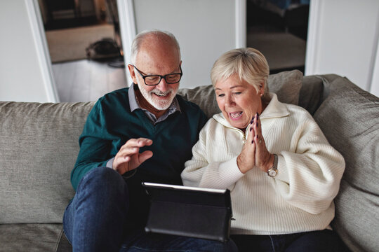 Smiling senior couple using digital tablet while sitting on sofa in living room