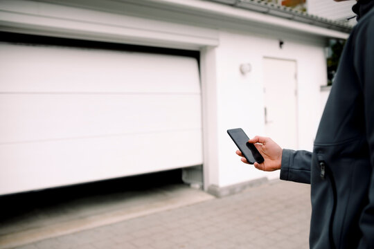 Midsection of teenage boy entering pin in smart phone while unlocking garage