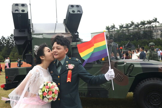 Chen Ying-Hsuan, a combat engineer lieutenant, and her wife Li Chen-Chen, take a photo in front of a AN/TWQ-1 Avenger mobile air defence system at a military mass wedding in Taoyuan