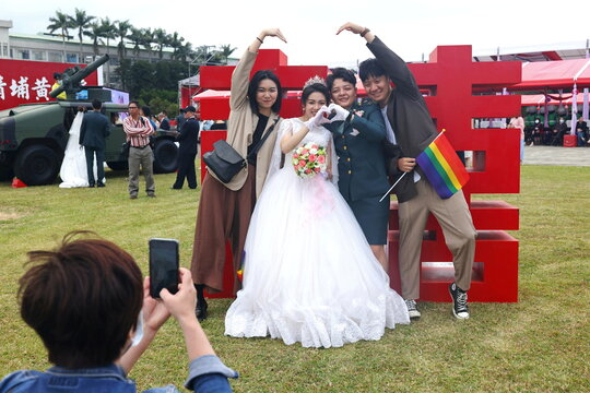 Chen Ying-Hsuan, a combat engineer lieutenant, and her wife Li Chen-Chen, take a group photo with their friends at a military mass wedding in Taoyuan