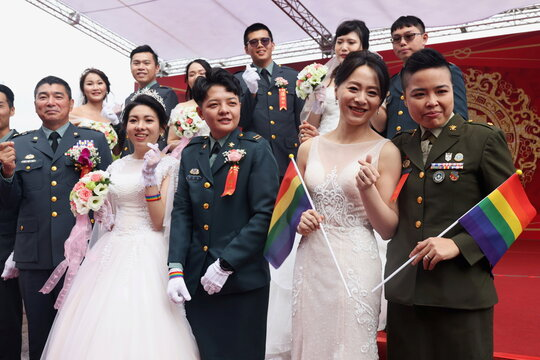 Two same-sex couples take a group photo during a military mass wedding in Taoyuan