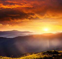 Wall Mural - Mystery mountains are illuminated by the sunset. Picture of colorful cloudy sky.