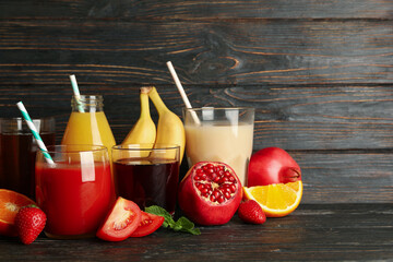 Glasses and jars with different juices on wooden background