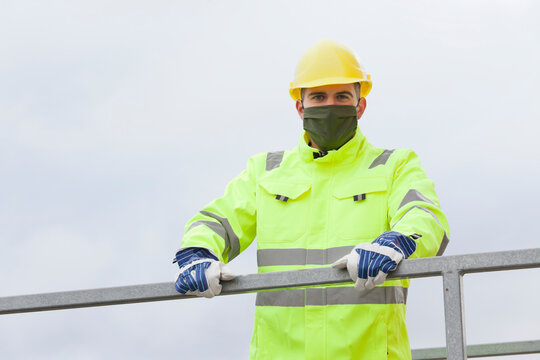 Portrait of smiling young engineer or worker with face mask and hard hat