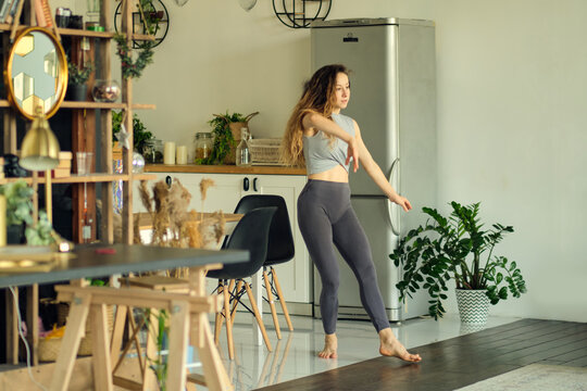 millennial girl wearing have fun moving listening to music relax in living room, happy young woman dance enjoy leisure weekend at home, stress free concept. Slow Motion video. Close up stock footage.