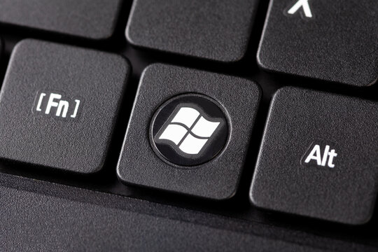 The Windows button on a black laptop notebook keyboard macro extreme closeup top view Round dedicated operating system key with white Windows logo 7/10