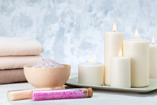 Spa composition with sea salt, bath towel and burning candles.