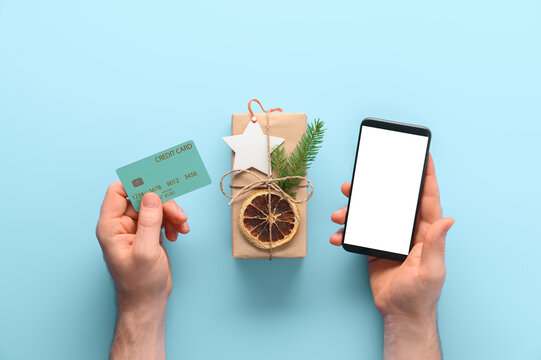 Christmas online shopping concept. Top view of male hands holding smartphone and credit card, gift on pastel blue background. A man buys gifts online. Flat lay.