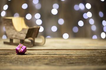 Fototapeta Dekoracja świąteczna - Boże Narodzenie, na stole, w oddali sanie Św. Mikołaja.  obraz