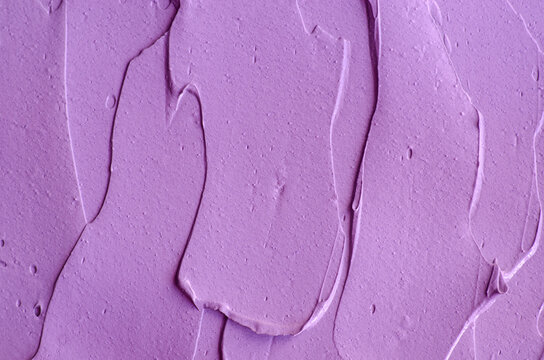 Purple clay (alginate face mask, body wrap, hair conditioner) texture close up, selective focus. Abstract lavender background with brush storkes.