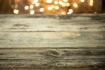 Obraz Pusty stół drewniany z rozmytym tłem ze światełkami i lampkami o ciepłej barwie na święta - fototapety do salonu