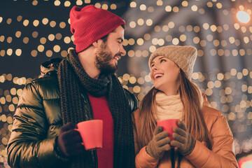 Photo of loving couple hold hot coffee beverage mug under x-mas evening illumination wear season tradition coats Fotomurales