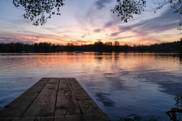 Wooden pier on the lake at sunset reflected in the water