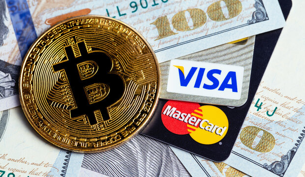 bitcoin cryptocurrency and Visa, MasterCard cards with money, dollars. Visa and MasterCard worldwide is an American multinational financial services corporation. Moscow, Russia - August 16, 2020