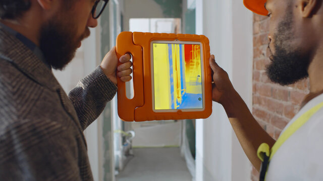 Back view of professional construction team using infrared camera on tablet checking heating system
