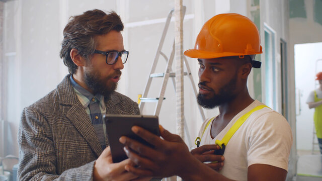 Portrait of caucasian architect and african builder discussing house blueprint on digital tablet