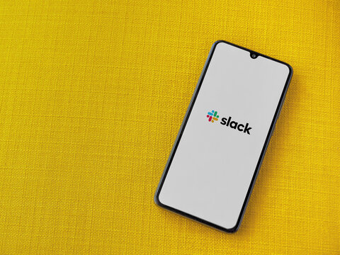 Lod, Israel - July 8, 2020: Slack app launch screen with logo on the display of a black mobile smartphone on a yellow fabric background. Top view flat lay with copy space.