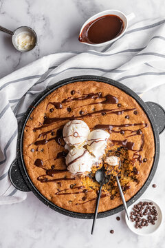 Skillet cookie with scoops of vanilla ice cream on a white marble background with drops of chocolate
