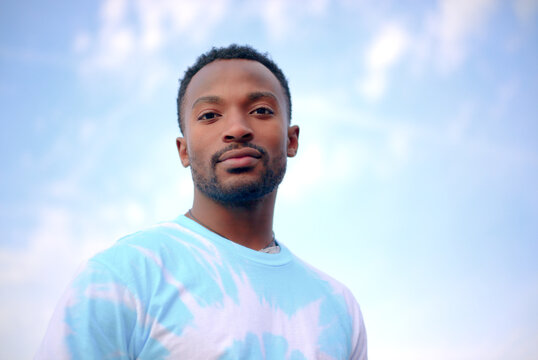 young spiritual man on blue cloudy sky tie and dye t-shirt