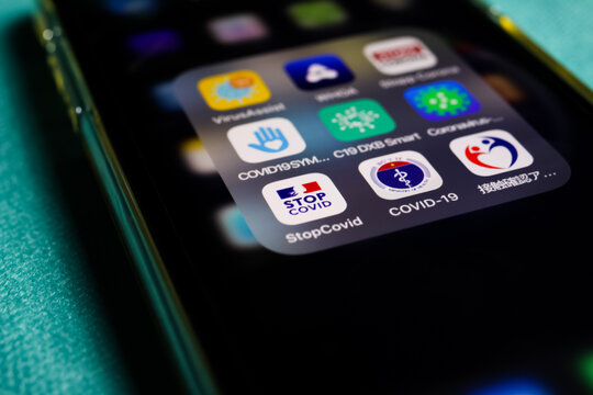 Viersen, Germany - July 7. 2020: Closeup of mobile phone screen with choice of international covid-19 apps. (Focus on french stop covid app left)