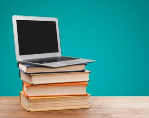 Stack of school books and laptop, education and learning concept