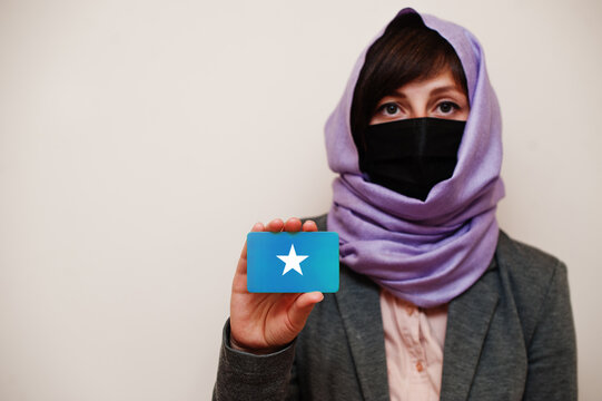 Portrait of young muslim woman wearing formal wear, protect face mask and hijab head scarf, hold Somalia flag card against isolated background. Coronavirus country concept.